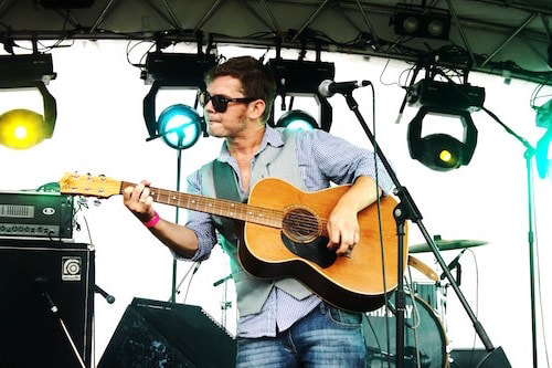 man playing guitar on a stage with a green light behind him asapentertainment noosa sunshine coast